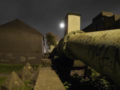 vandalised gas pipe near grass at night - stock photo