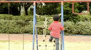 Stock Video Footage of Boy climbing on a rope ladder in a playground