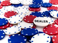 red white and blue poker chips and dealer chip - stock photo