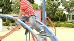 Boy climbing on climbing frame in a park Stock Footage