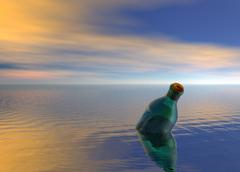 message in a bottle floating on ocean - stock photo