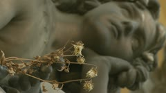 Cemetery statue holding dead flowersv(rack focus 2) Stock Footage
