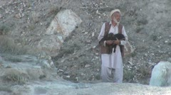 A Pakistani villager carries a baby sheep home Stock Footage