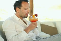 Happy young man drinking exotic cocktail in lounge bar NTSC - stock footage