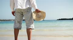 Man with summer hat standing on the beach HD Stock Footage