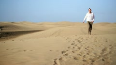 Young happy man walking on the desert HD - stock footage