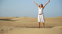 Woman with wide open arms standing on the desert HD Stock Footage