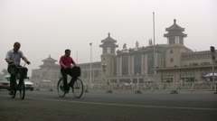 China people cycle past Beijing Railway station and through heavy smog - stock footage