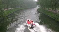 Speedboat sails through a canal in Beijing, China Stock Footage