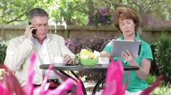 Husband and wife on the phone and tablet - stock footage