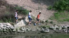Kids are playing alongside a polluted stream in Beijing, China Stock Footage