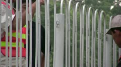 Close up of two workers painting a fence on the roadside in China Stock Footage