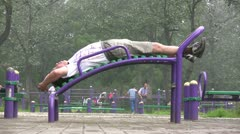 A Chinese man stretches his back on a public excercise machine Stock Footage