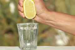 Female hand squeeze a lemon into glass Stock Footage
