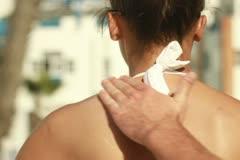 Man applying sun block lotion on woman's back, steadicam shot Stock Footage