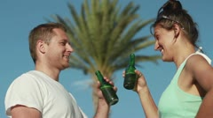 Couple drinking beer in exotic hotel, outdoors, steadicam shot Stock Footage