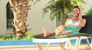 Woman talking on cellphone on sunbed, steadicam shot Stock Footage