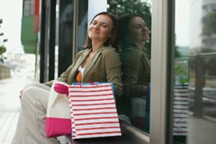 Smiling woman with shopping bags sitting by shop window NTSC Stock Footage