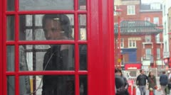 In red telephone box in London on phone Stock Footage
