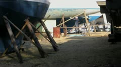 Man working on boat in yard Stock Footage