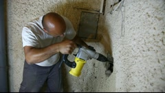 Construction plumber drills big hole to fix leaking water pipes MRL Stock Footage