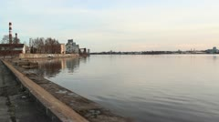 Calm water riverside with industrial buildings in background Stock Footage