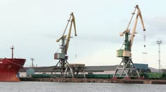 Cranes at harbour with train passing by Stock Footage