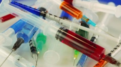 Many multicolor syringes rotating on blue Stock Footage