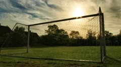 Sun moving behind soccer goalposts in Europe - stock footage
