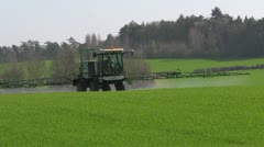 Crop spraying - fertilizer - backlit, green field and trees. Stock Footage