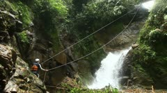 Footage of a person crossing a waterfall on a zip line locked down, wide angle Stock Footage