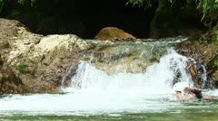 Group of two young people swimming and jumping into an Ecuadorian rainforest - stock footage