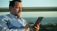 Businessman sitting outdoors and using tablet computer  HD Stock Footage