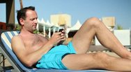 Young man sending sms while sunbathing by the pool HD Stock Footage