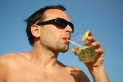 Young man having a drink against blue sky NTSC Stock Footage