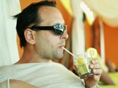 Young smiling man drinking exotic cocktail in luxury bar  NTSC Stock Footage