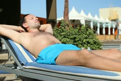 Handsome man sunbathing on sunbed by the pool NTSC Stock Footage