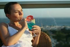 Young woman having drink on terrace with beautiful view NTSC Stock Footage