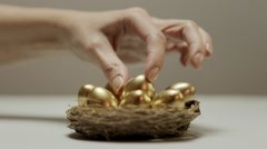Golden eggs in nest, woman securing savings and precious things - stock footage