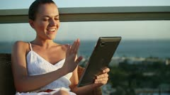 Smiling woman chatting on tablet while relaxing on terrace HD - stock footage