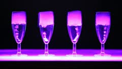 Four nice glasses with gurgle drink, colorful illumination Stock Footage