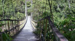 Walking the Rickety Hanging Suspension Bridge Stock Footage