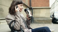 Woman drinking coffee and talking on cellphone, outdoors, steadicam shot HD Stock Footage