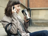 Woman drinking coffee and talking on cellphone, outdoors, steadicam shot NTSC Stock Footage