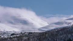 Clouds rolling over snowy mountains time lapse Stock Footage