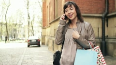 Woman with shop bags talking on the phone in the city, steadicam shot HD Stock Footage