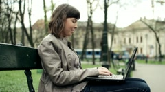Attractive woman with laptop in the park, steadicam shot HD - stock footage
