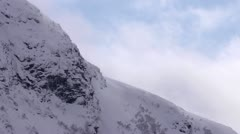 Clouds rolling behind snow covered mountains time lapse Stock Footage