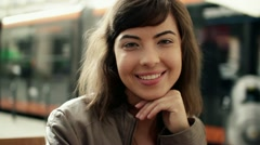 Attractive smiling happy woman sitting by city street, steadicam shot HD Stock Footage