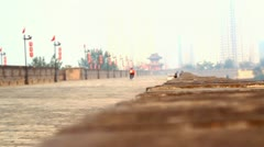 Biker on ancient Xian City Wall on a foggy day, China Stock Footage